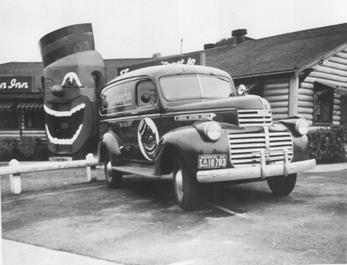 """To the left of the photo, you can see the """"coon"""" that served as the front door to the Coon Chicken Inn. You walked in through the mouth of the caricature. Directly in front is a """"coon car."""" These vehicles were used for delivery."""